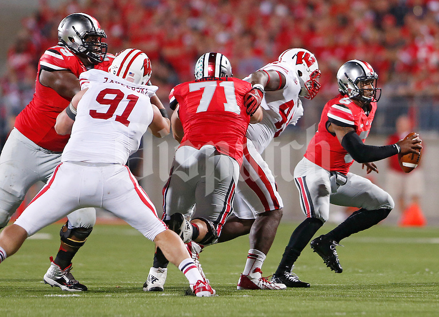 Ohio State Buckeyes quarterback Braxton Miller (5) eludes a Wisconsin rush in the second half at Ohio Stadium on September 28, 2013.  (Chris Russell/Dispatch Photo)