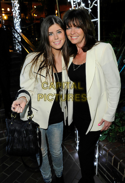"VICKI MICHELLE (R) & daughter LOUISE.at the film premiere of ""Dirty Oil"", Barbican Centre, London, England, UK, 15th March 2010..half 3/4 length white cream jacket family mother mum mom bag jeans black top trousers smiling shoulder pads blazer .CAP/FIN.©Steve Finn/Capital Pictures"
