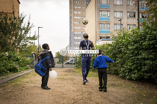 Homes for Haringey & Keepmoat Regeneration community event, London Borough of Haringey, London UK - children playing football with Tottenham Hotspur Foundation worker