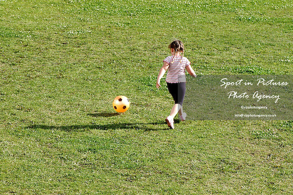 A young girl playing football