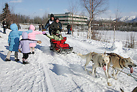 The Walton family, from Eagle River, including Kacie, Marie and Morgan, give high-fives to  Peter Bartlett and his Iditarider Valerie Conin along the trail near Tudor Road in Anchorage on Saturday March 1st during the ceremonial start day of the 2008 Iidtarod Sled Dog Race.