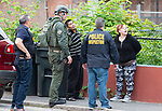 WATERBURY,  CT-051719JS13-  Officers detain residents from a home on East Liberty Street as they search the home as part of a city-wide operation on Friday. Waterbury Police, with cooperation State Police, Watertown Police, the States Attorney's Office, the DEA and ATF conducted search and seizures as well as searching for wanted suspects who police say were suspected in the sale of heroin.<br /> Jim Shannon Republican American