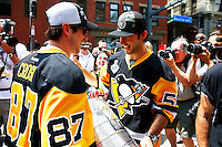 Kris Letang #58 of the Pittsburgh Penguins hands the Stanley Cup to teammate Sidney Crosby #87 of the Pittsburgh Penguins on Boulevard of the Allies during the victory parade in downtown Pittsburgh, Pennsylvania on June 15, 2016. (Photo by Jared Wickerham / DKPS)