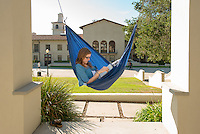 Lani Cupo '18 takes a break from studying for finals to read in a hammock outside the Samuelson Pavilion (The Tiger Cooler) on Dec. 9, 2014. (Photo by Marc Campos, Occidental College Photographer)