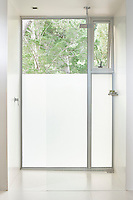 A simple shower located in a box that seems to pop out of the back of the house. For privacy, the lower part of the glass is obscure.