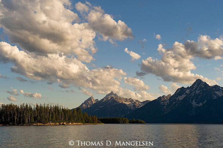 Jackson Lake is backdropped by the Tetons, while clouds scatter the sky at sunset in Grand Teton National Park, Wyoming.