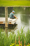 Clinton inlet. Man fishing for crabs from dock.