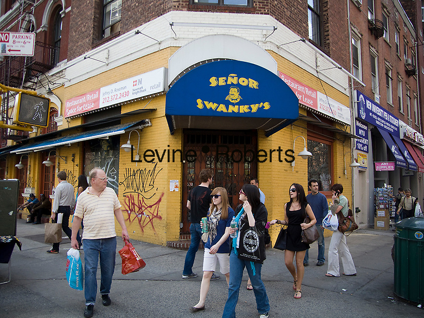Pedestrians walk past a closed Senor Swanky's Mexican Restauarant on Bleecker Street in the New York neighborhood of Greenwich Village on Saturday, April 18, 2009. (© Richard B. Levine)
