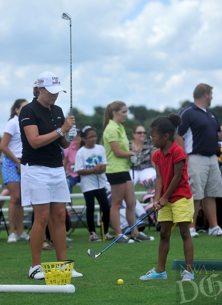 NWA Media/Michael Woods --06/24/2014-- w @NWAMICHAELW...Pro Golfer Cristie Kerr gives some golf tips to Aidan Booker, age 8 from Centerton, Tuesday afternoon during the First Tee girls only clinic in Lowell.  The hour long clinic gave local aspiring young female golfers a chance to meet and ask Kerr questions and get tips on their golf game.