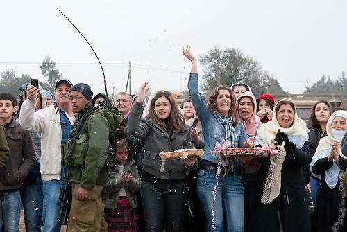 Plateau du Golan, dans la zone tampon entre la Syrie et Israel, Jan 2011. Dans le cadre de la reunification familiale facilitee par le CICR (Comite International de la Croix Rouge), un mariage a lieu entre une Syrienne et un  Israelien de la comunaute druze, qui est separee des deux cotes de la frontiere. Des proches saluent les maries. Le temps d'une petite heure, c'est une occasion unique de revoir des parents qui vivent de l'autre cote de la frontiere depuis qu'Israel a annexe le Golan en 1981 (annexion non reconnue a ce jour par l'ONU). Seul le CICR est habilite a coordoner ce genre de reunion, car la frontiere est fermee pour les civils.