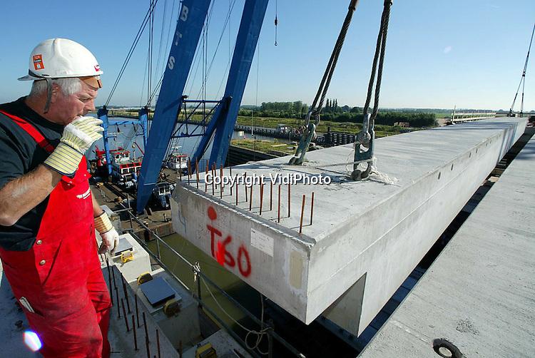 Foto: VidiPhoto..TIEL - Bij de viaducten in aanbouw over het Amsterdam-Rijnkanaal in Tiel worden donderdag en vrijdag door Romein Beton uit Dodewaard 38 enorme betonnen overspanningen (liggers) geplaatst. Het gaat om de zwaarste liggers (80 ton) die voor de viaducten in de Betuweroute worden gebruikt. Bij Tiel komen zowel een nieuwe verkeersbrug (A15) als een nieuwe spoorbrug (Betuwelijn). De middenoverspanningen worden geplaatst met een drijvende bok. Opdrachtgever is de Bouwcombinatie BR4, de uitvoerder van de Betuwelijn. Eind dit jaar moeten de viaducten gereed zijn. Eind augustus volgen nog eens 38 liggers.