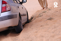 Man standing by car stuck in sand in desert, low section (Licence this image exclusively with Getty: http://www.gettyimages.com/detail/sb10065474dr-001 )