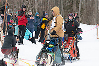 Nils Hahn and team run past spectators on the bike/ski trail near University Lake with an Iditarider in the basket and a handler during the Anchorage, Alaska ceremonial start on Saturday, March 7 during the 2020 Iditarod race. Photo © 2020 by Ed Bennett/Bennett Images LLC