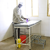 A member of the staff of Marie Stopes International cleans an operating table before other staff members will perform several sterilization procedures as part of a scheduled visit to the Cholga health center on August 24, 2010 in rural Ethiopia.