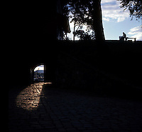 Man sitting on a bench silhouetted against the sky, showing arch with wooden doors and cobbled walkway below.
