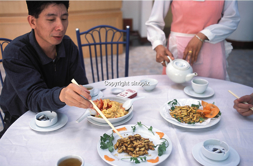 "A customer eats at the ""Fresh Wildlife"" restaurant in Guangzhou, that specializes in selling various insects including potato grubs,  earth worms, scorpions, water beetles and bee larvae...PHOTO BY SINOPIX"
