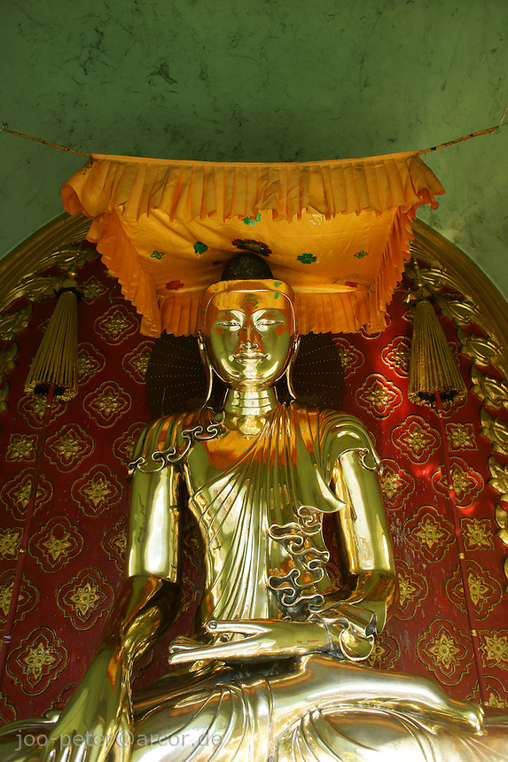 golden buddha sculpture in a shrine in Sula Paya pagoda complex, center of Yangon, Myanmar, 2011