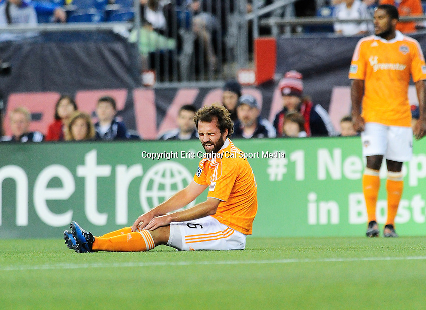 MAY 19 2012 Houston Dynamo midfielder Adam Moffat #16 sits on the field in pain after getting tangled up with New England Revolution midfielder Shalrie Joseph #21...