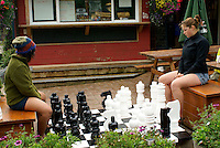 Young women playing chess on a large outdoor chess board, Snug Cove,   Bowen Island, British Columbia, Canada