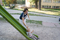 Toddler letting anxious mom help him down park slide ages 28 and 1. Balucki District Lodz Central Poland