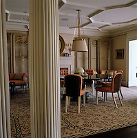 Seen through the pillared entrance the spacious dining room; warmth comes from the dining chairs upholstered in coral and a modern floral rug