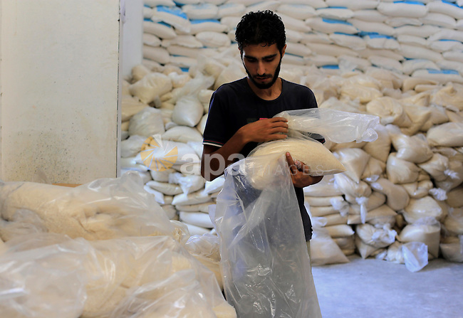 A Palestinian man carries bags of rice at a distribution centre of the United Nations Relief and Works Agency (UNRWA) in Gaza City on August 11, 2014. An Israeli delegation arrived in Cairo for indirect negotiations with Palestinians on a durable truce in Gaza, Egypt and Israeli officials said. Photo by Mohammed Asad