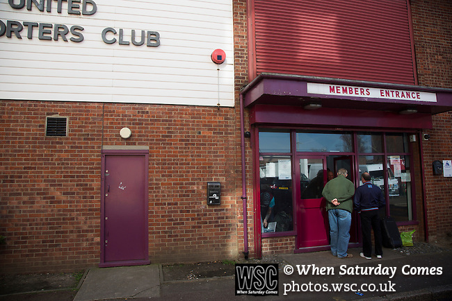 West Ham United 2 Crystal Palace 2, 02/04/2016. Boleyn Ground, Premier League. Two men waiting at the entrance to the supporters club building on Castle Street outside the Boleyn Ground before West Ham United hosted Crystal Palace in a Barclays Premier League match. The Boleyn Ground at Upton Park was the club's home ground from 1904 until the end of the 2015-16 season when they moved into the Olympic Stadium, built for the 2012 London games, at nearby Stratford. The match ended in a 2-2 draw, watched by a near-capacity crowd of 34,857. Photo by Colin McPherson.