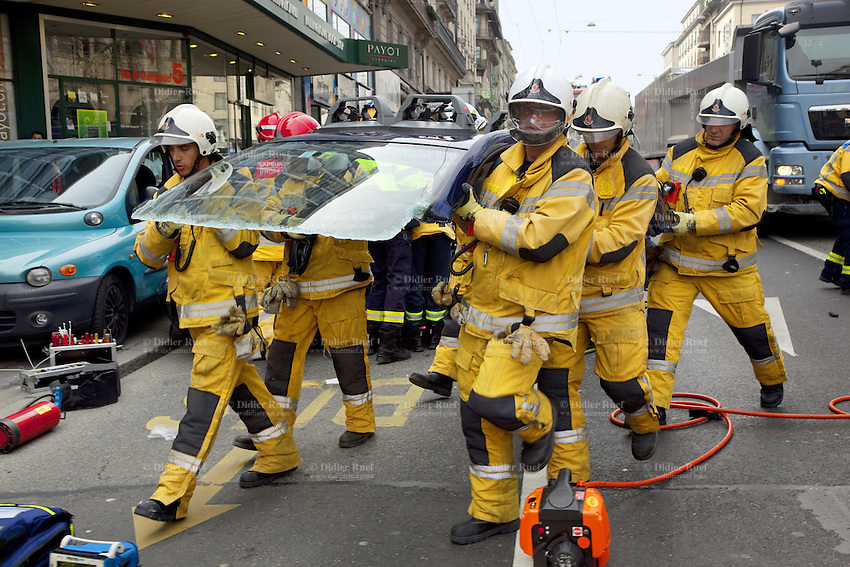 Switzerland. Geneva. Paquis neighborhood. Car accident on  the Chantepoulet street. Firefighters with helmets and yellow protective clothing work on a vehicle extrication, which is the process of removing a vehicle from around a person who has been involved in a motor vehicle accident, when conventional means of exit are impossible or inadvisable. A delicate approach is needed to minimize injury to the victim during the extrication. This operation is typically accomplished by using hydraulic tools, such as a cutter. The cutter is a hydraulic tool which is designed to cut through metal - a hydraulically powered shears. It is often called a crab-cutter, owing to the shape and configuration of its blades. Sometimes specified as to its capacity to cut a solid circular steel bar, these are most commonly used to cut through a vehicle's structure in an extraction operation. Cutter blades are replaceable, and blade development progresses as vehicle technology progresses in order to be able to cope with the new car protection technology. 21.03.12 © 2012 Didier Ruef..