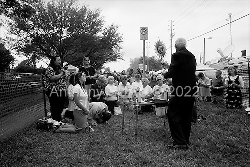 Pinellas Park, Florida.USA.March 24, 2005..Protesters hold a mass for the help of Governor Jeb Bush, Republican-Florida, to step in and save the life of Terri Schiavo outside the Woodside Hospice where Schiavo is a patient. The press covers the event in forces with live broadcasts and satellite feeds...The U.S. Supreme Court rejected a plea from the parents of Terri Schiavo to restart her feeding, leaving them nearly out of options and time in the seven-year legal fight for their brain-damaged daughter's life.