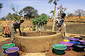 The Gambia. Women drawing water from a well for watering crops in the vegetable garden; colourful bowls.