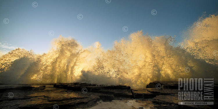 waves splash as they crash against the rocky coastline at sunset