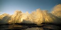 waves splash as they crash against the rocky coastline at sunset