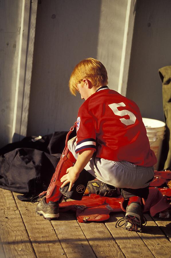 Red-headed boy in red baseball uniform adjusting equipment, Oak Harbor, Washington