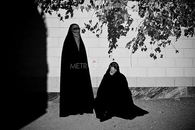 KHORRAMABAD, IRAN : Women in traditional clothes, chador, who have taken a vow of silence to mark the festival of Ashura...Every year to mark the death of Imam Hussein, Shia Muslims mourn for two days. In Khorramabad and Lorestan in the west of Iran, during the first day of mourning, called Tasooa, women take a vow of silence and go through the streets with the children lighting candles. At 4 am on Ashura, the second day, men cover themselves in mud and then stand in front of a fire until the mud has dried to clay. After this they go to the mosque and pray...Photo by Farhad Babaei/Metrography