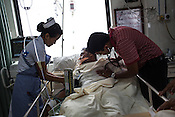 A doctor checks the status of a patient at the intensive care unit of the Duncan Hospital in Raxaul, Bihar, India.
