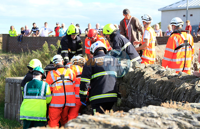 Members of Clogherhead Coast Guard assist with a female casualty that had fallen from a wall onto rocks at Clogherhead pier, Fire service were required to assist in the extraction with paramedics from National Ambulance Service, the casualty was removed to Our Lady of Lourdes Hospital in Drogheda.<br /> Picture Thos Caffrey www.newsfile.ie