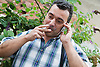 Bulgarian man outside in garden using a mobile phone whilst smoking,
