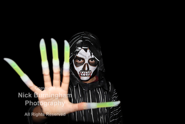 Young boy dressed as a scary ghoul with face paint and long fingernails on Halloween - with copy space