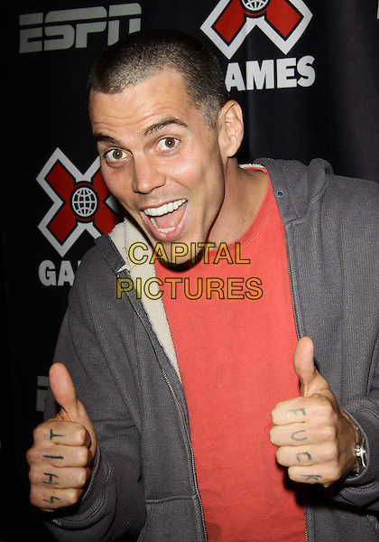 "STEVE O (Stephen Gilchrist Glove).""The Birth of Big Air""  Los Angeles Premiere held at Regal Theater LA, Los Angeles, California, USA..July 27th, 2010.half length top jacket thumbs up shit fuck knuckles mouth open red grey gray.CAP/ADM/TC.©T. Conrad/AdMedia/Capital Pictures."