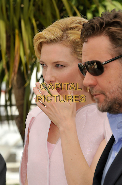 """CATE BLANCHETT & RUSSELL CROWE.""""Robin Hood' photocall.63rd International Cannes Film Festival, France.12th May 2010.headshot portrait hand profile stubble facial hair  pink sunglasses shades side blue black.CAP/PL.©Phil Loftus/Capital Pictures."""