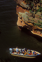 A small power boat explores the sea caves at Squaw Point in the Apostle Islands National Lakeshore near Bayfield, Wis.