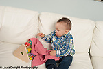 9 month old baby boy sitting on couch pulling cloth off hidden toy Piaget Opject permanence
