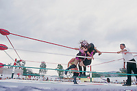 Amapola lunges at her opponent in a Lucha Libre match in Ecatepec, Estado de Mexico. June 2004