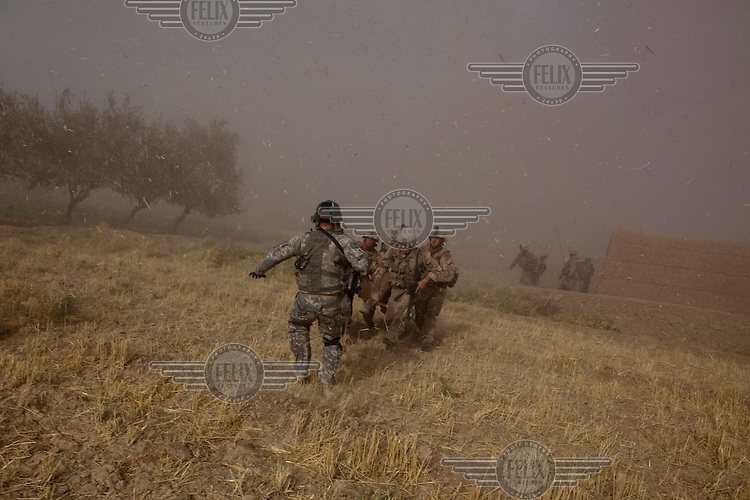 Flight Medic SFC James Shields from Charlie Company, Sixth Battalion, 101st Aviation Regiment runs to assist a wounded marine from his US Army medevac helicopter near Marja.