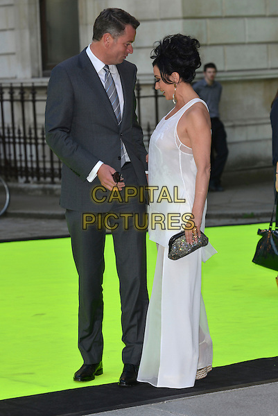 guest &amp; Nancy Dell'Olio<br /> Royal Academy Summer Exhibition Preview Party 2013, London, England 5th June 2013<br /> full length grey gray suit white sheer top trousers side profile clutch bag<br /> CAP/PL<br /> &copy;Phil Loftus/Capital Pictures