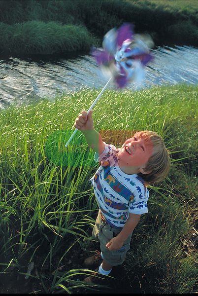 young boy laughing and playing with pinwheel