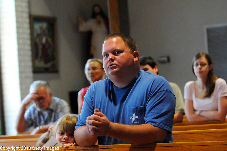 LAFITTE, LA - JUNE 20:  Jason Cox and his daughter Kaitlyn Cox listen during mass at St. Anthony Church on a day designated a day of prayer in response to the Gulf oil spill, June 20, 2010 in Lafitte.   (Photo by Cheryl Gerber/Getty Images).