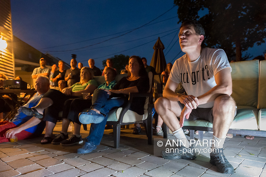 """Merrick, New York, USA. 11th June 2017.  """"American Grit"""" TV contestant CHRIS EDOM (wearing white  GOT GRIT? T-shirt), 48, of Merrick, hosts backyard Viewing Party for Season 2 premiere. Edom family relatives and neighbors watched Episode 1 of FOX network reality television series that Sunday night outdoors. Edom was last contestant picked for a team that episode."""
