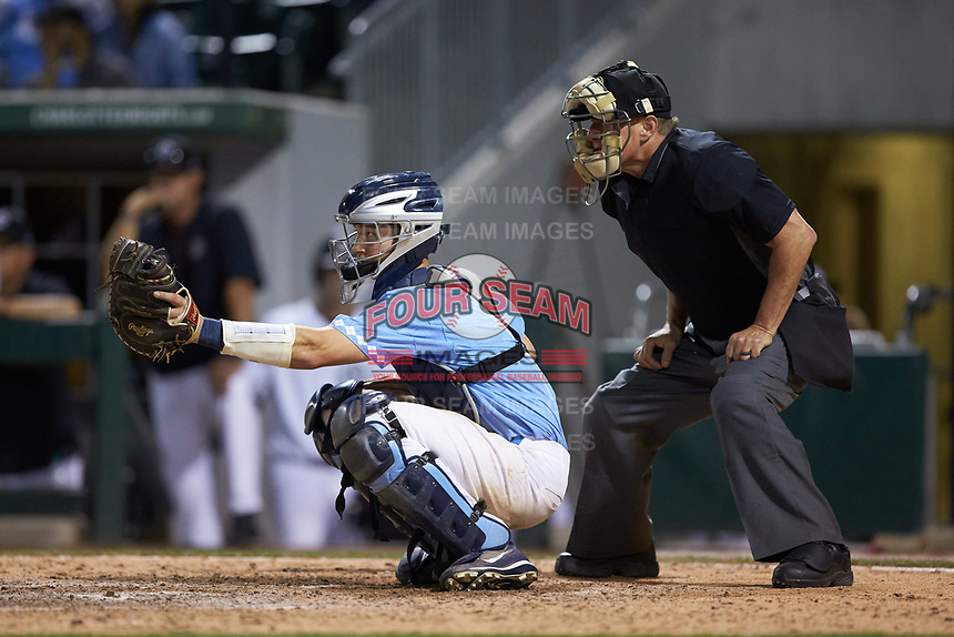 Home plate umpire David Savage stands behind North Carolina Tar Heels catcher Cody Roberts (11) against the South Carolina Gamecocks at BB&T BallPark on April 3, 2018 in Charlotte, North Carolina. The Tar Heels defeated the Gamecocks 11-3. (Brian Westerholt/Four Seam Images)