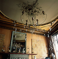 A gold dining room has a mirror set above an ornate fireplace. A delicate metal chandelier hangs from a ceiling with gilded cornices.